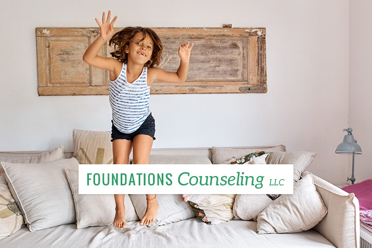 Young girl jumping on couch with arms above head