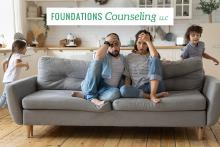 Stressed parents on couch with rowdy kids
